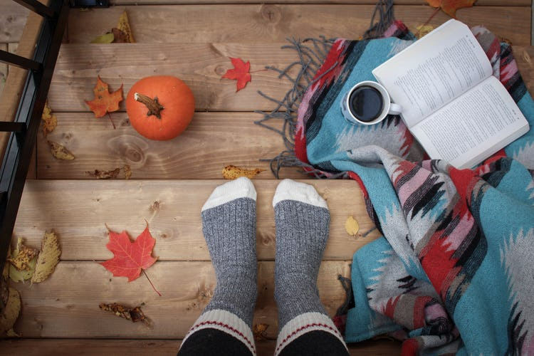 Person wearing gray socks, standing on wooden steps strewn with fall leaves. A pumpkin, cup of coffee, book, and blanket are on steps, too.