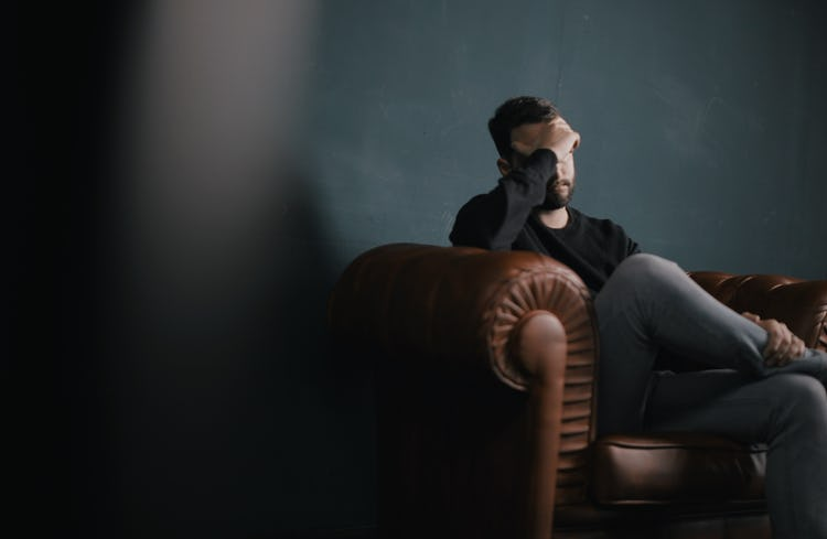 A man sitting in a therapist's office and looking sad.