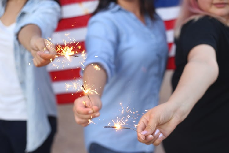 Three women celebrating the Fourth of July with sparklers.