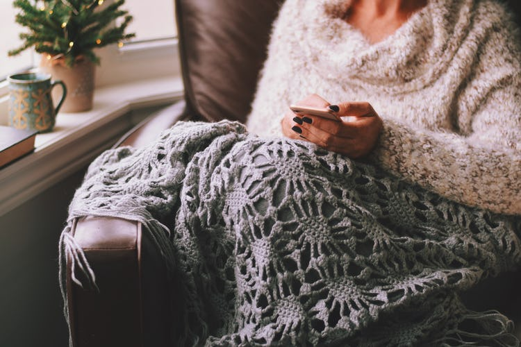 a woman checking email on her phone while sitting beneath blanket on the couch