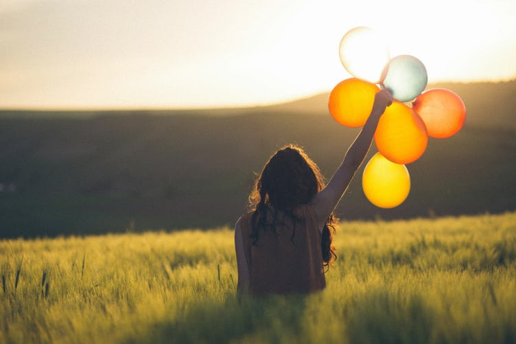 A woman in a field facing the mountains and holding up a group of balloons in her hand.