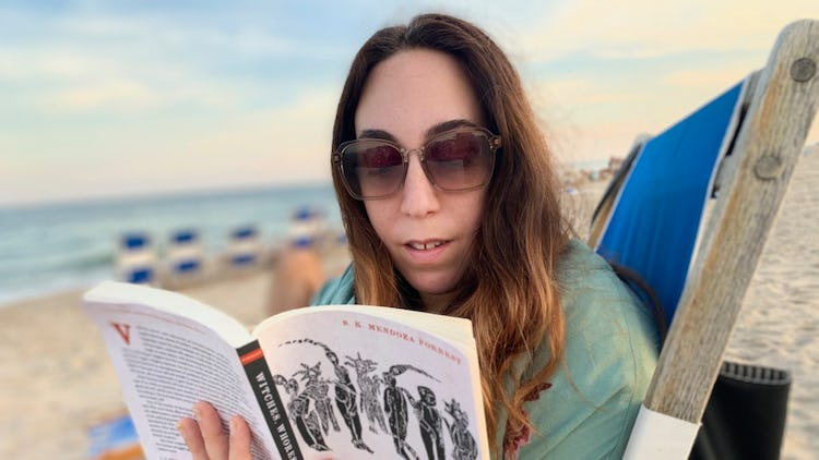 Kelly Showker reading a book on the beach, instead of drinking.