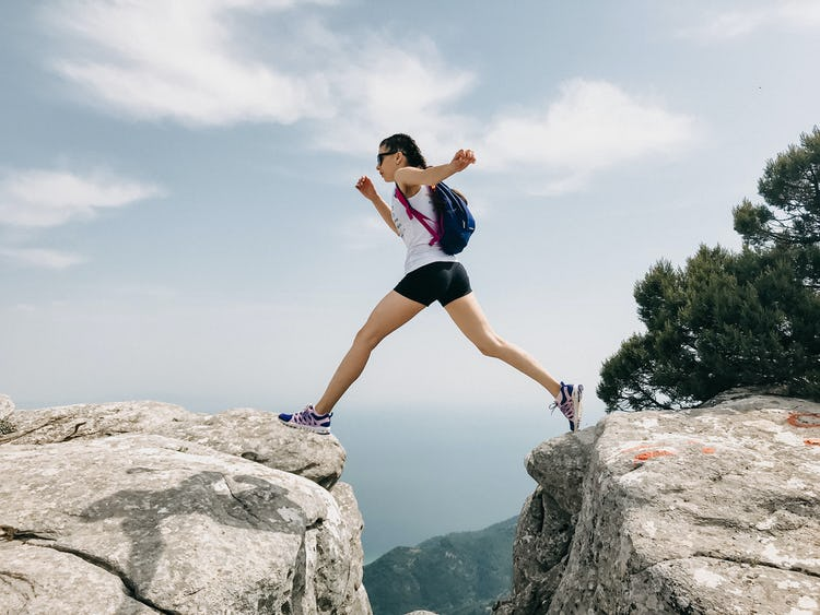 A woman jumping over a gap in the mountains.