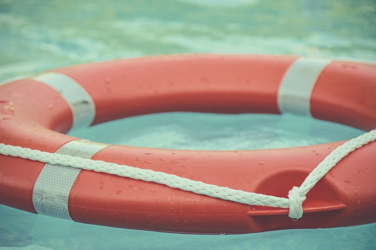 An orange and white ring buoy floating in water