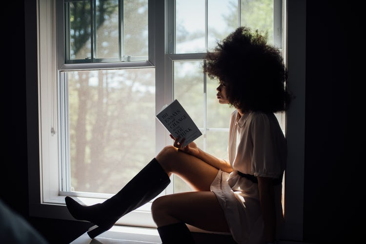 Black woman sitting on a windowsill and reading a recovery memoir.