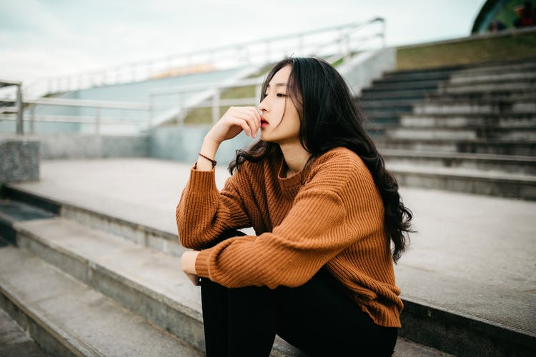 An Asian American woman sitting on steps and thinking about quitting drinking.