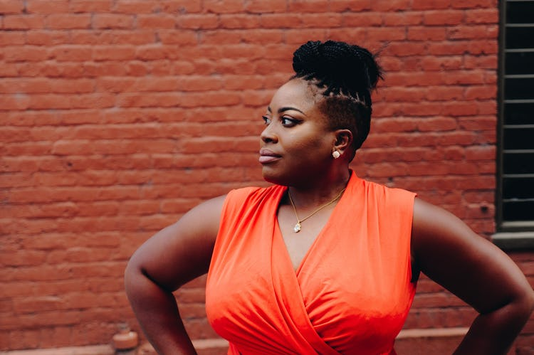 Black woman with a bun and orange dress standing against a brick wall.