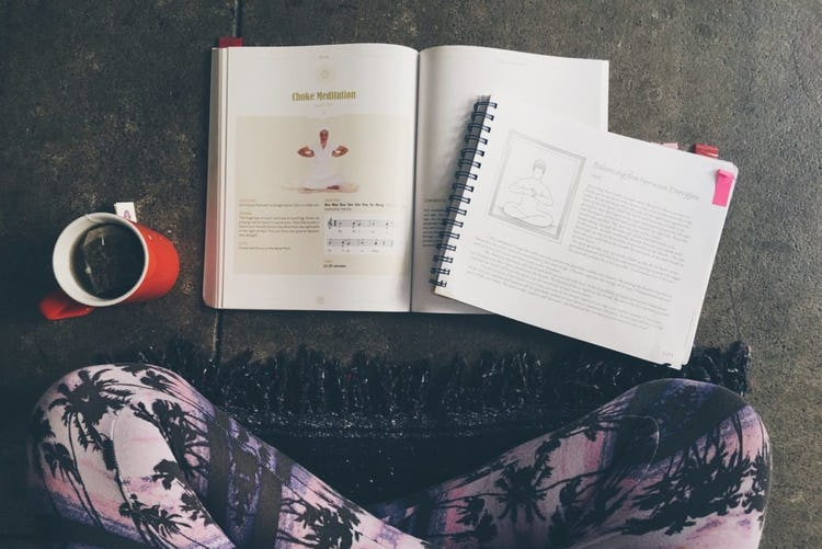 the author sitting in leggings with a copy of coffee and yogic text