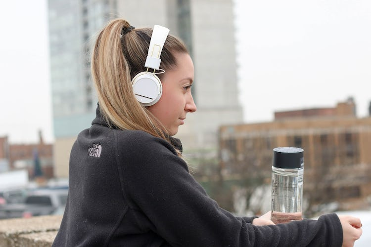 A fair-skinned woman listening to headphones and holding a water bottle as she looks out onto the city