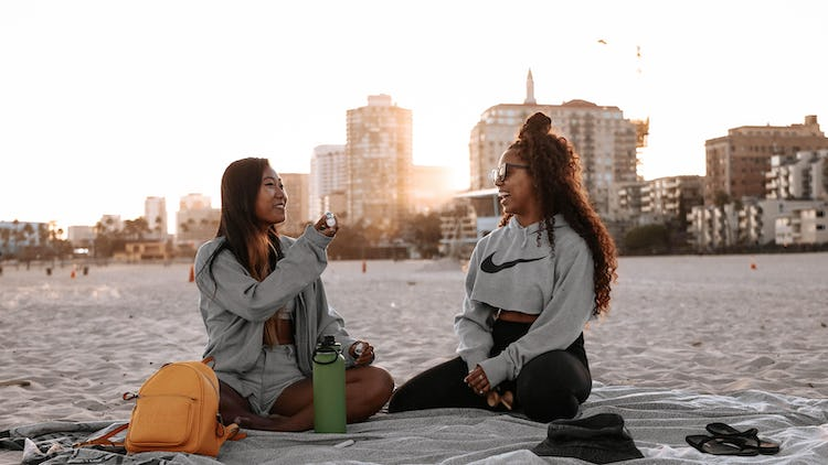 Two women laughing on the beach and having fun as friends.