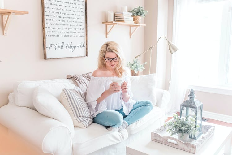 White woman sitting on a couch and relaxing while drinking tea.