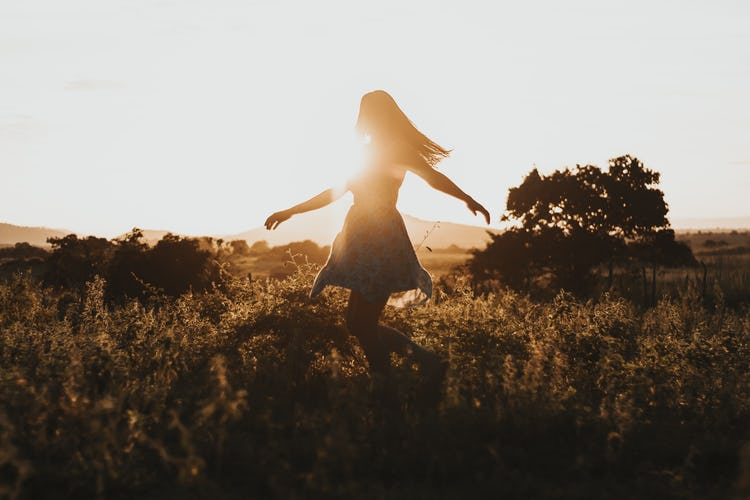 a woman dancing in a field at sunset celebrating the benefits of sobriety