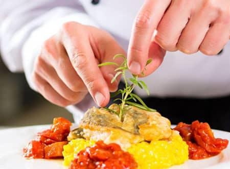 chef colocando alecrim na comida