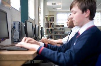 School boys in uniform working on computer stations in school