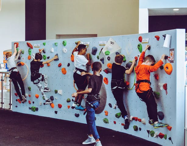Students climbing on a rock climbing wall