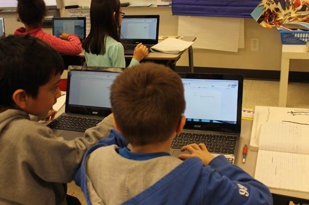 School kids in a classroom working on laptops