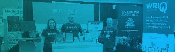 Texthelpers Kaitlyn, Jason and Mark standing in front of the booth at the ILA Conference