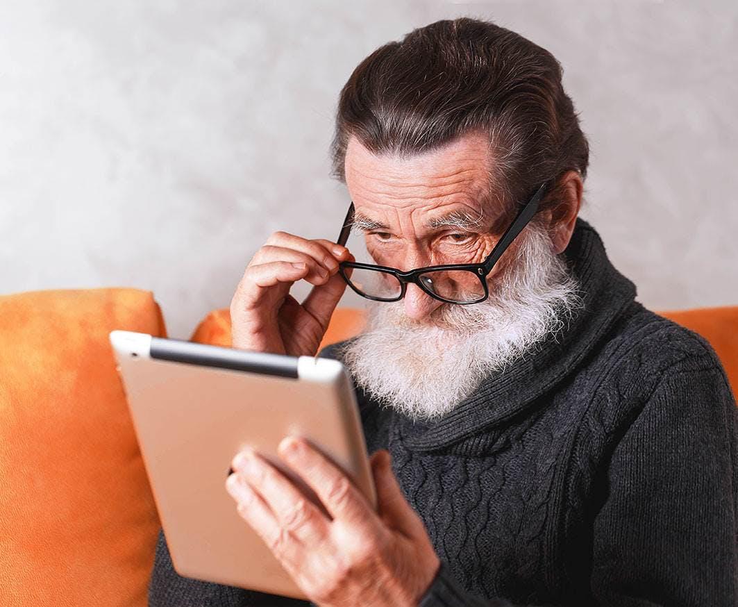 elderly man reading on a tablet