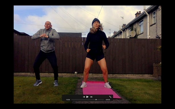 Angela and her partner Brian working out in their back garden, displayed on a laptop screen