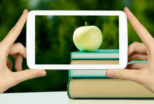Smartphone camera being held by a pair of hands, taking an picture of an apple on a stack of books