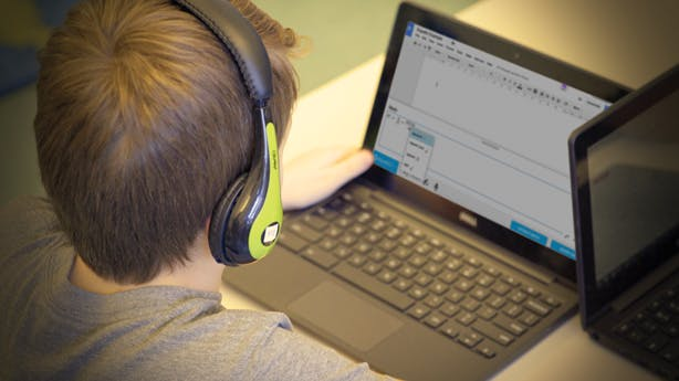 Boy with black and green headphones using EquatIO on a laptop