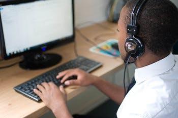 Boy in school uniform wearing headphones working on a computer