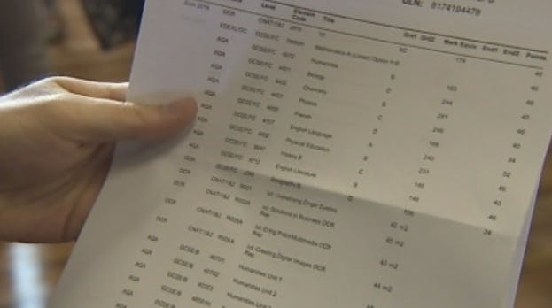 School grades results sheet being held in someone's hand