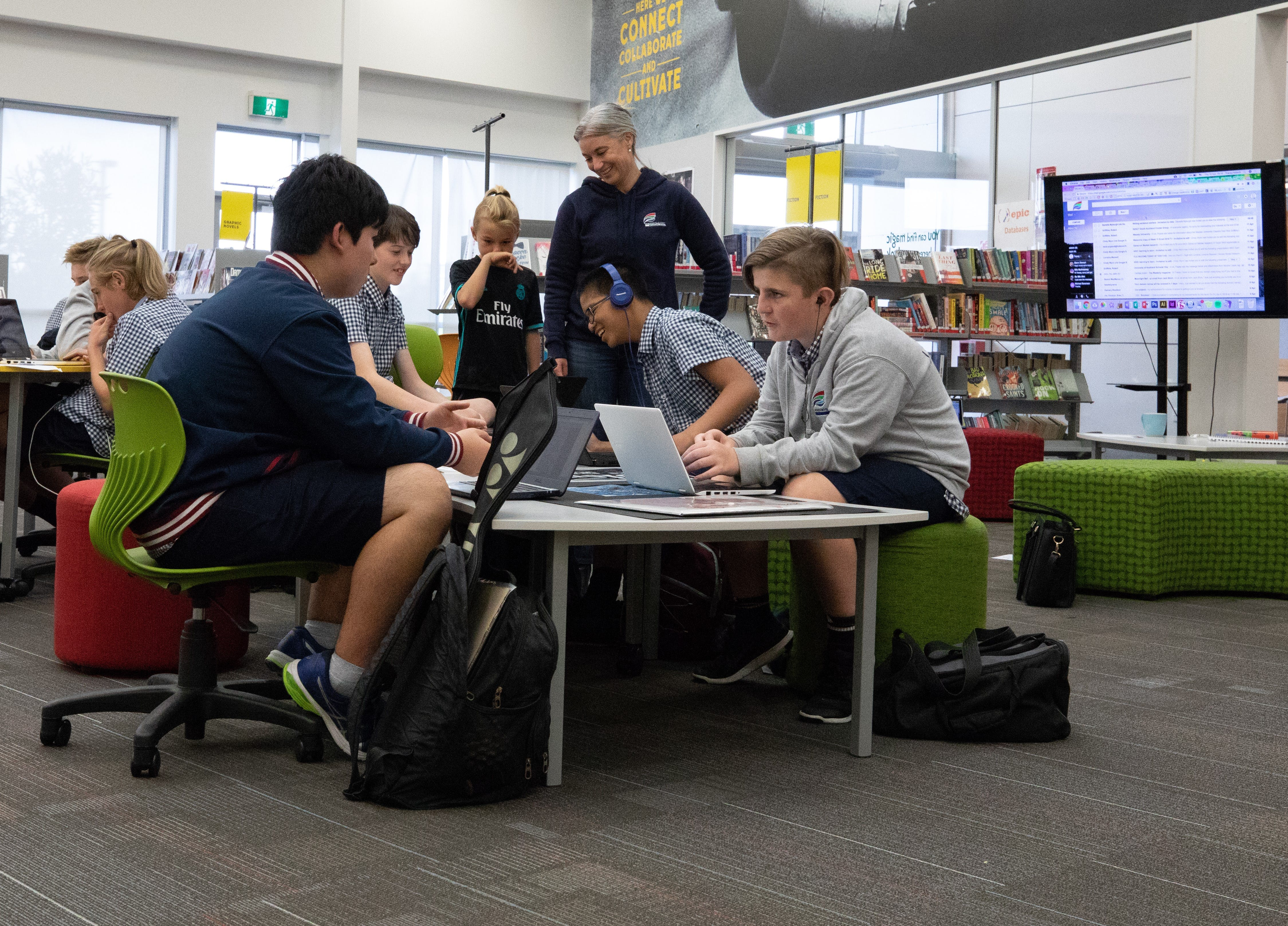 A teacher and her students working collaboratively on their devices at Hobsonville Point Secondary School