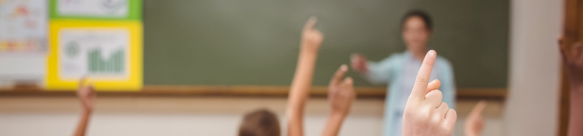Children with their hands up in class