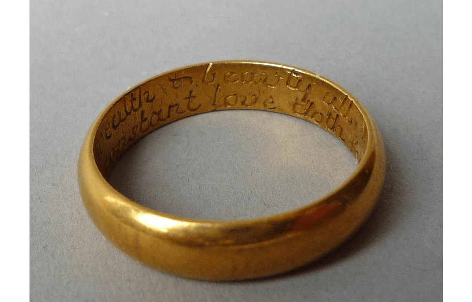 Gold ring on a neutral surface. The ring is photographed from an angle so that an internal inscription is partially visible