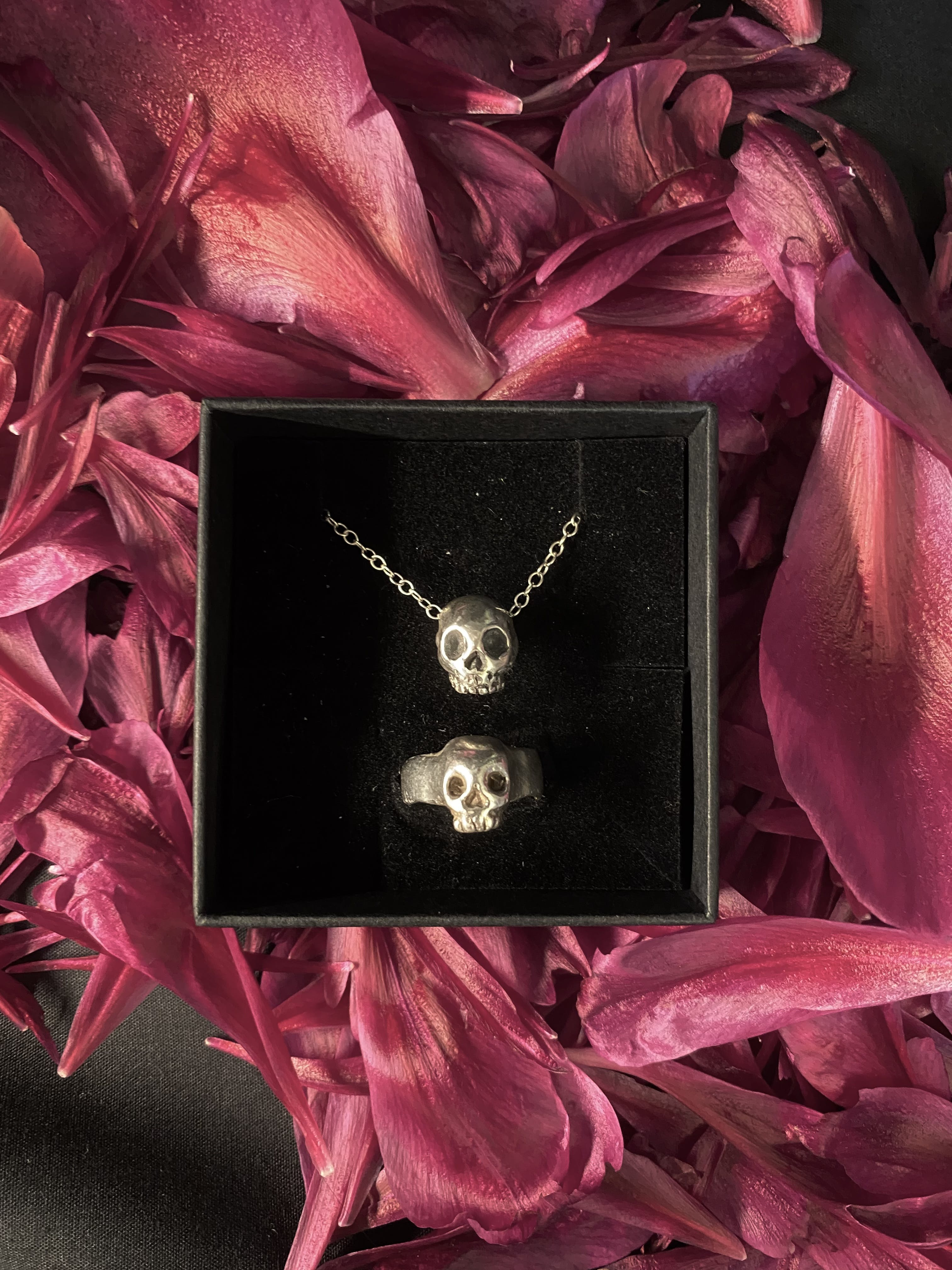 A small skull face on a chain in a black box which also contains a skull face on a small ring. The box sits on a pile of flower petals
