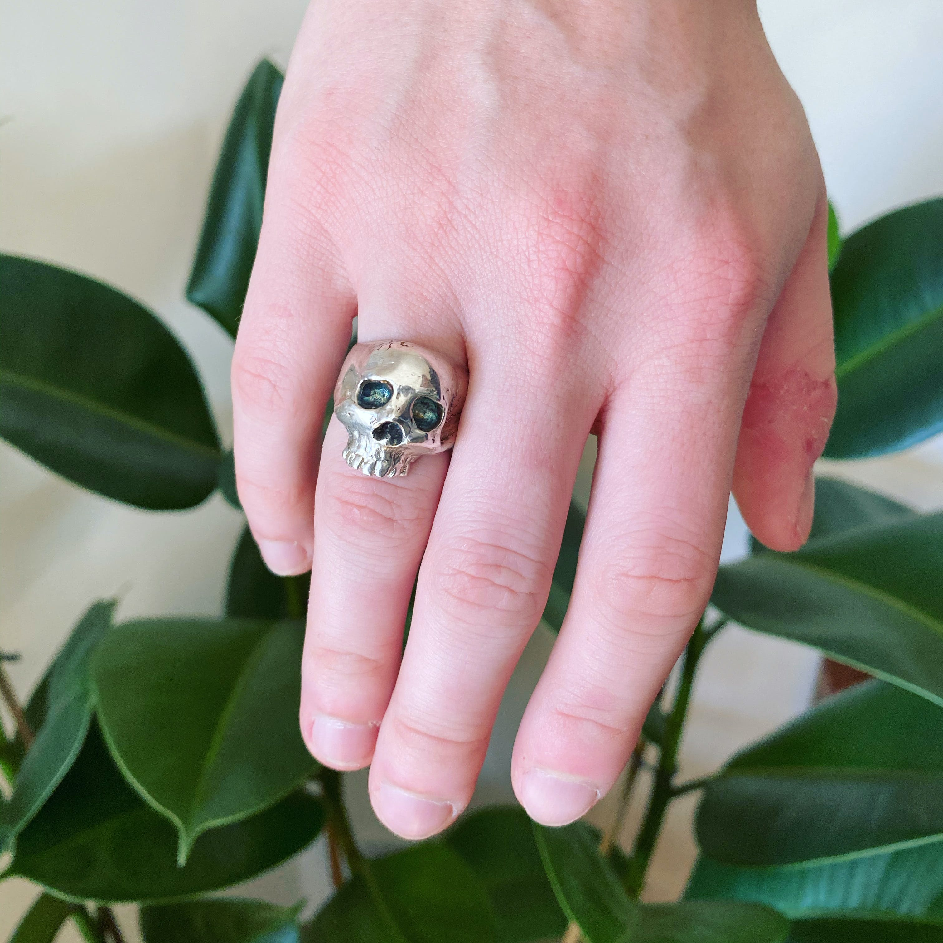 A hand with a large skull ring on the ring finger. The skull is shiny silver metal with dark grey eye and nose sockets, some small dark cracks can be seen on the upper corner.