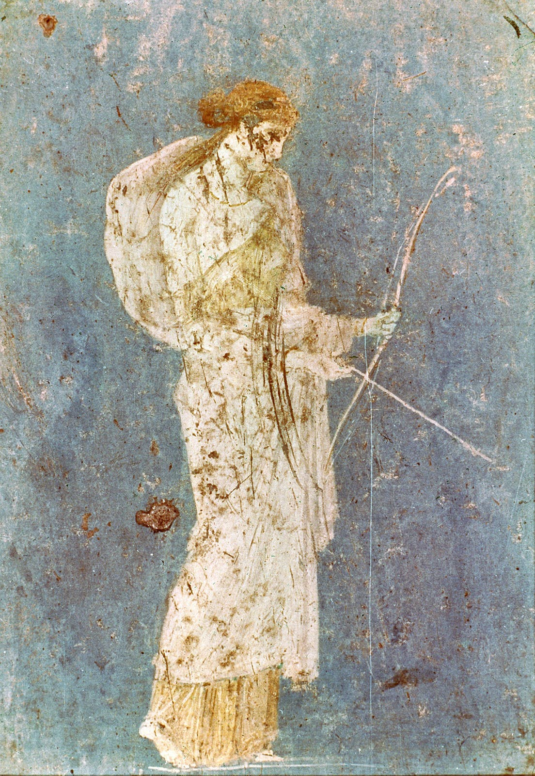 An old and damaged wall painting of a woman in white holding a bow and arrow on a blue background.