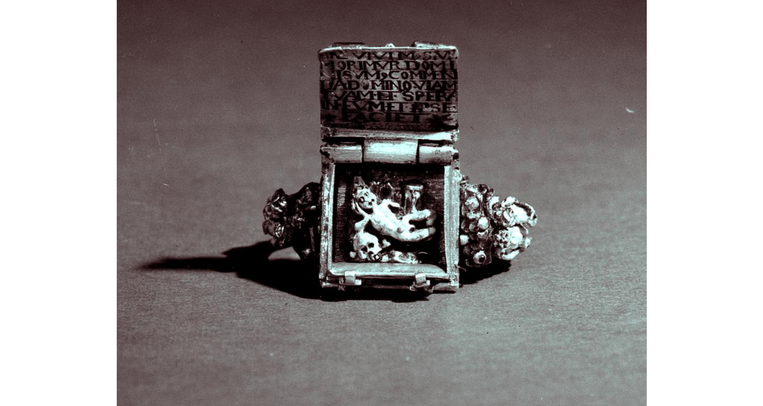 Memento Mori finger ring, shown with the book face open to reveal a languishing figure and black lettering.