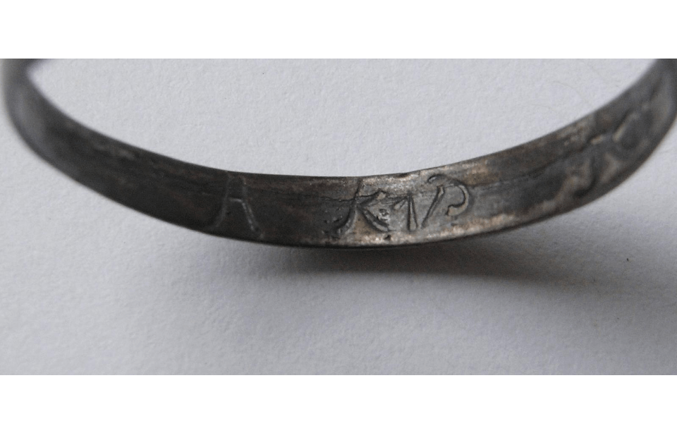 A blackened looking ring, photographed so the inside is visible, with a partial inscription reading 'A Kiss'