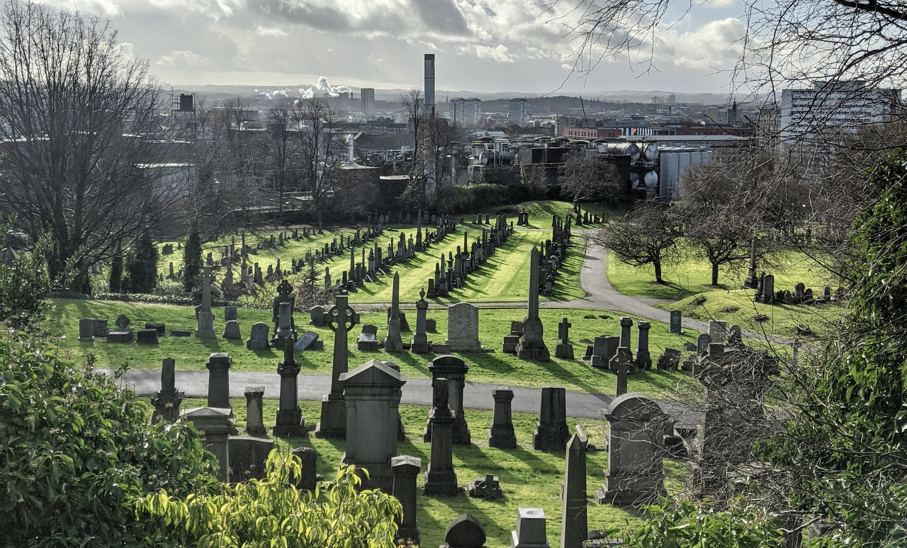 Landscape photo taken from a hill overlooking a large gravestone, with Glasgow city in the background under grey clouds.