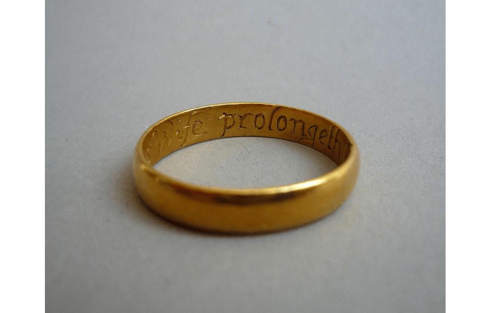 Gold ring on a neutral surface. The ring is photographed from an angle so that an internal inscription is partially visible reading '...wife prolongeth...'