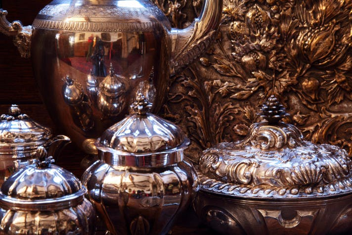 A close up photograph of a collection of silver items, ornate pots with lids and highly reflective surfaces.