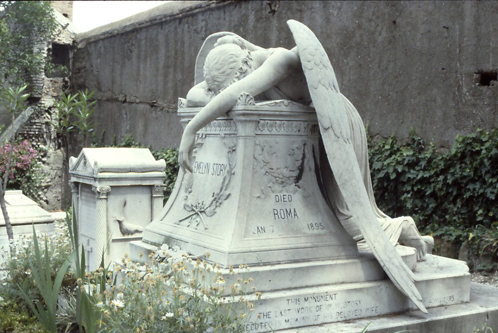 A large ornate tombstone made from a white stone with the name Evelyn Story on the front. Draped across the stone is a carving of a weeping angel laying face down.