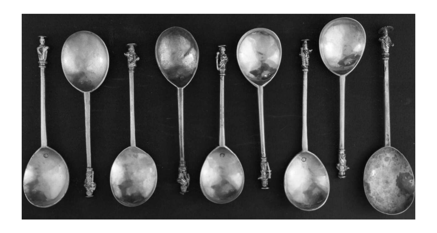 set of nine silver spoons with tiny human figures on the end of the handles.