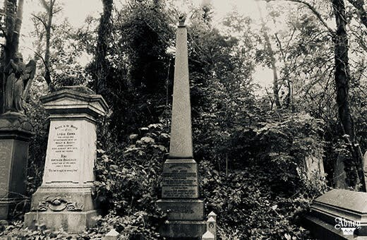 Black and white photo of some tall graves in front of trees. The centre stone is a tall obelisk with a hand in the shape of a fist at the very to