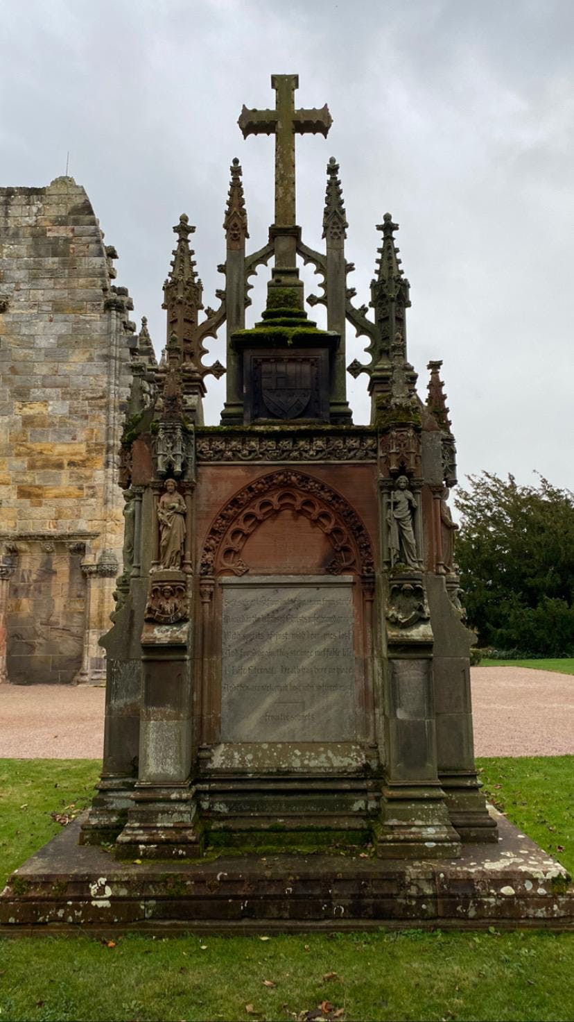 A very large and ornate stone with an inscription in the centre, made from red and grey stone. There are repeated archway patterns from the top of the inscription carved into the stone, to a spire-looking top section which has a large ornate cross at the very top. There are carved figures stood either side, making the stone look like a mini cathedral.