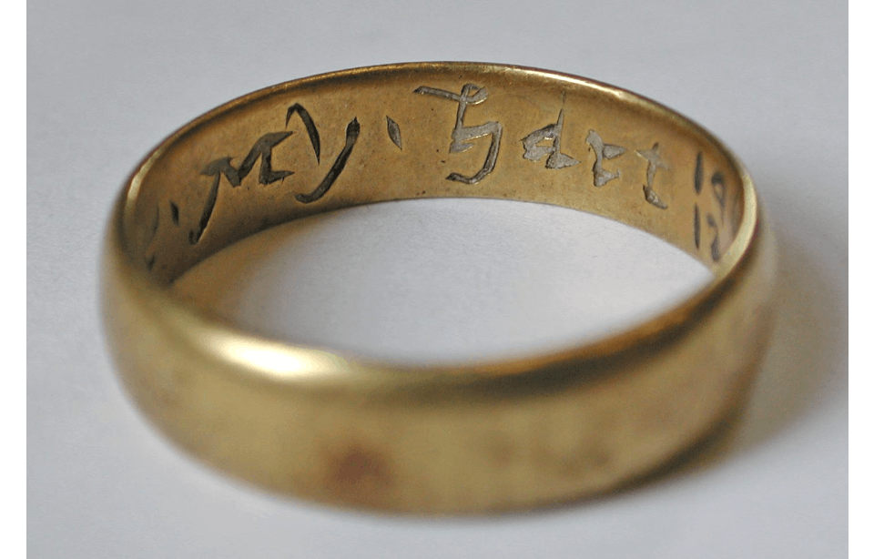 A  gold ring sits on a neutral background, the item is photographed at an angle from above showing a section of the inscription with simple but pretty engraving which says ' My - hart '