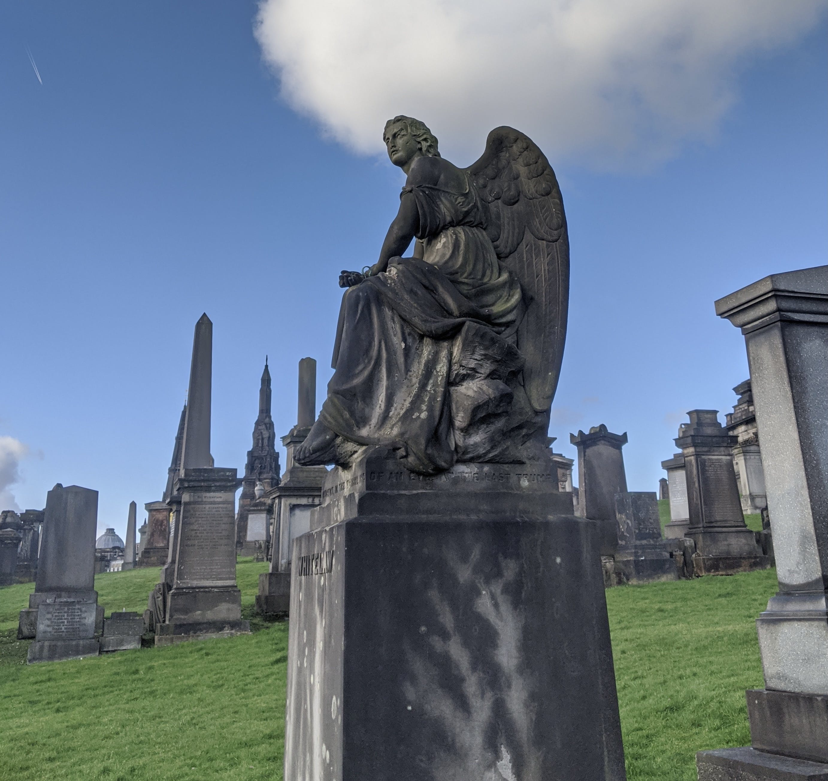 A graveyard on a sunny day, in the centre of the image is a large block grave marker with a huge angel sitting atop.