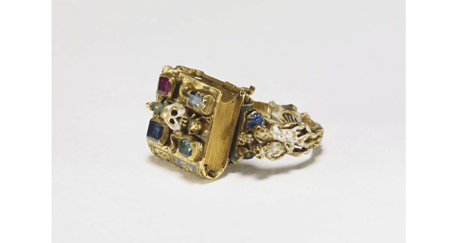 Memento Mori finger ring, showing a skull on top of a book made from gold and precious stones