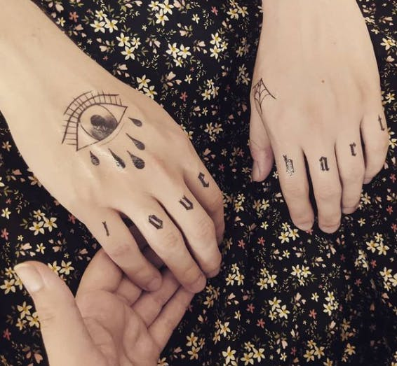 Two hands showing a temporary tattoo of a crying eye on one and a spiderweb on the other, with 'love hart' spelled out on the knuckles, on a floral black backdrop.