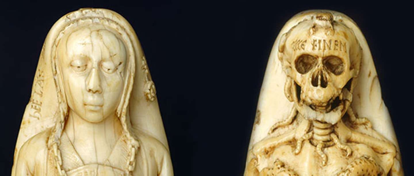 Memento mori carved ivory pommel. View of young woman on the front and cadaver on reverse
