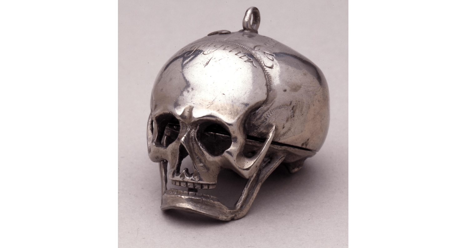 Silver skull watch with cursive engravings on top of head.