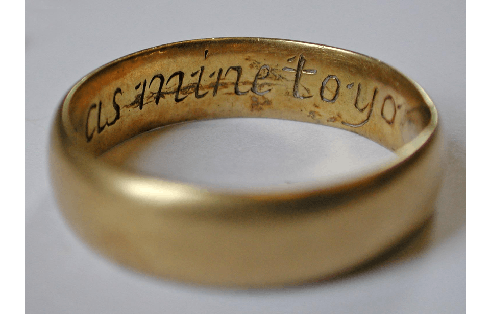 Gold ring with an engraved inscription visible on the inside in a rounded script which reads 'mine to you' from the angle we can see it from.