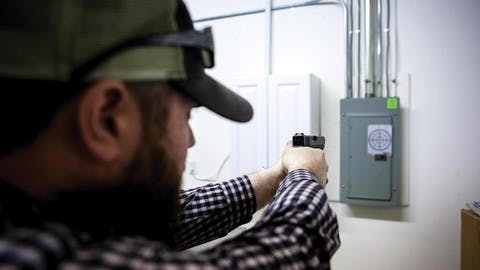 Chris Jones aims his pistol at a bullseye on the wall